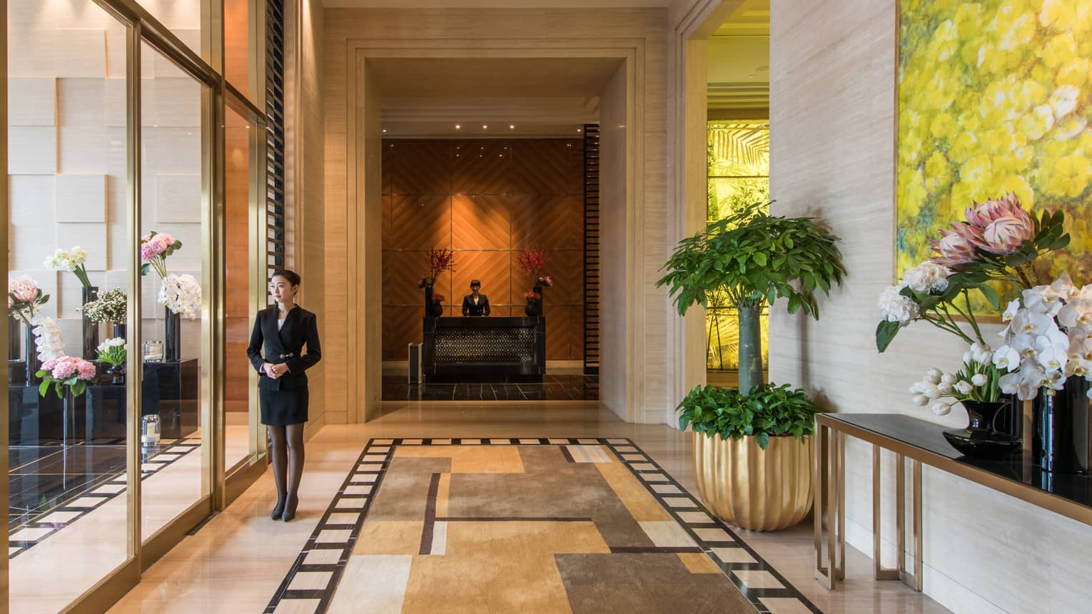 Concierge stands by sliding glass doors at residence entrance, lobby