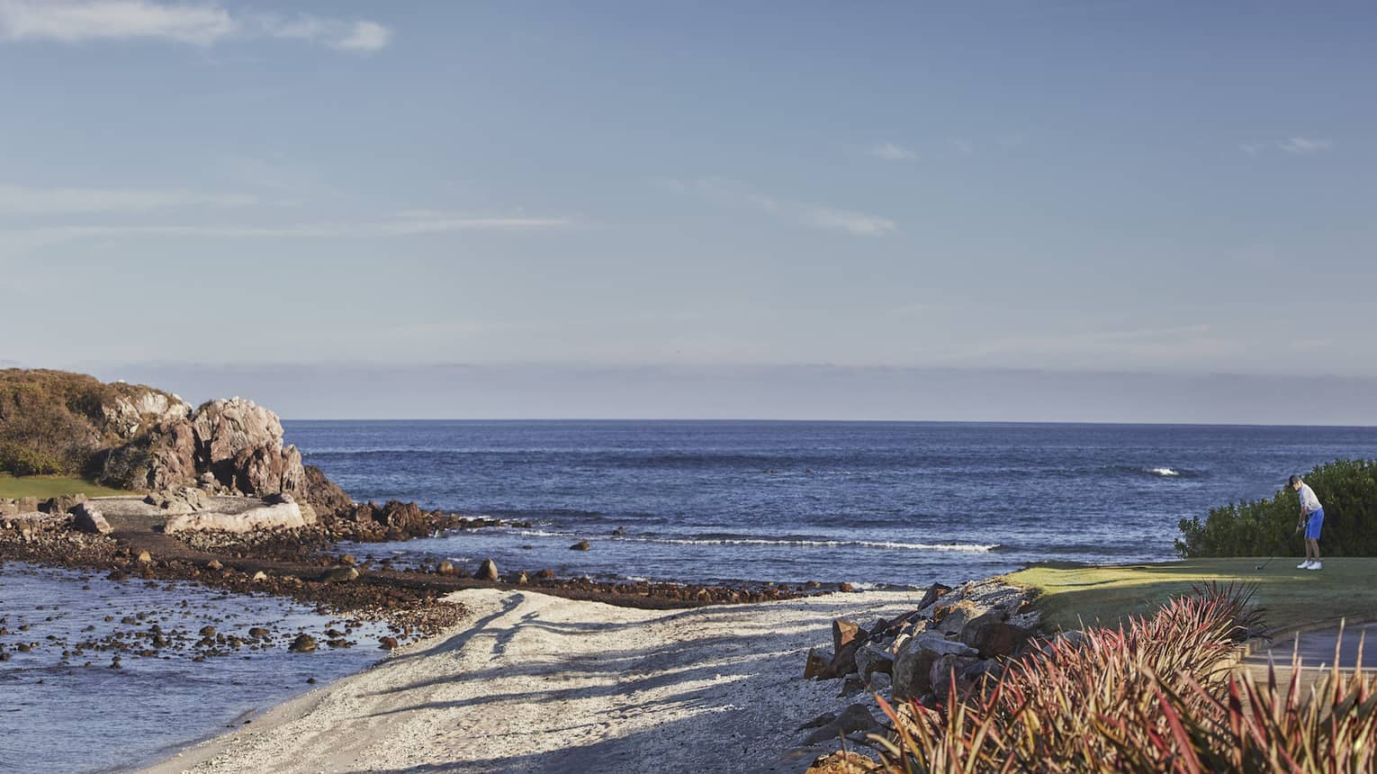 Sweeping view of golf course greens extending onto rocky island along coast