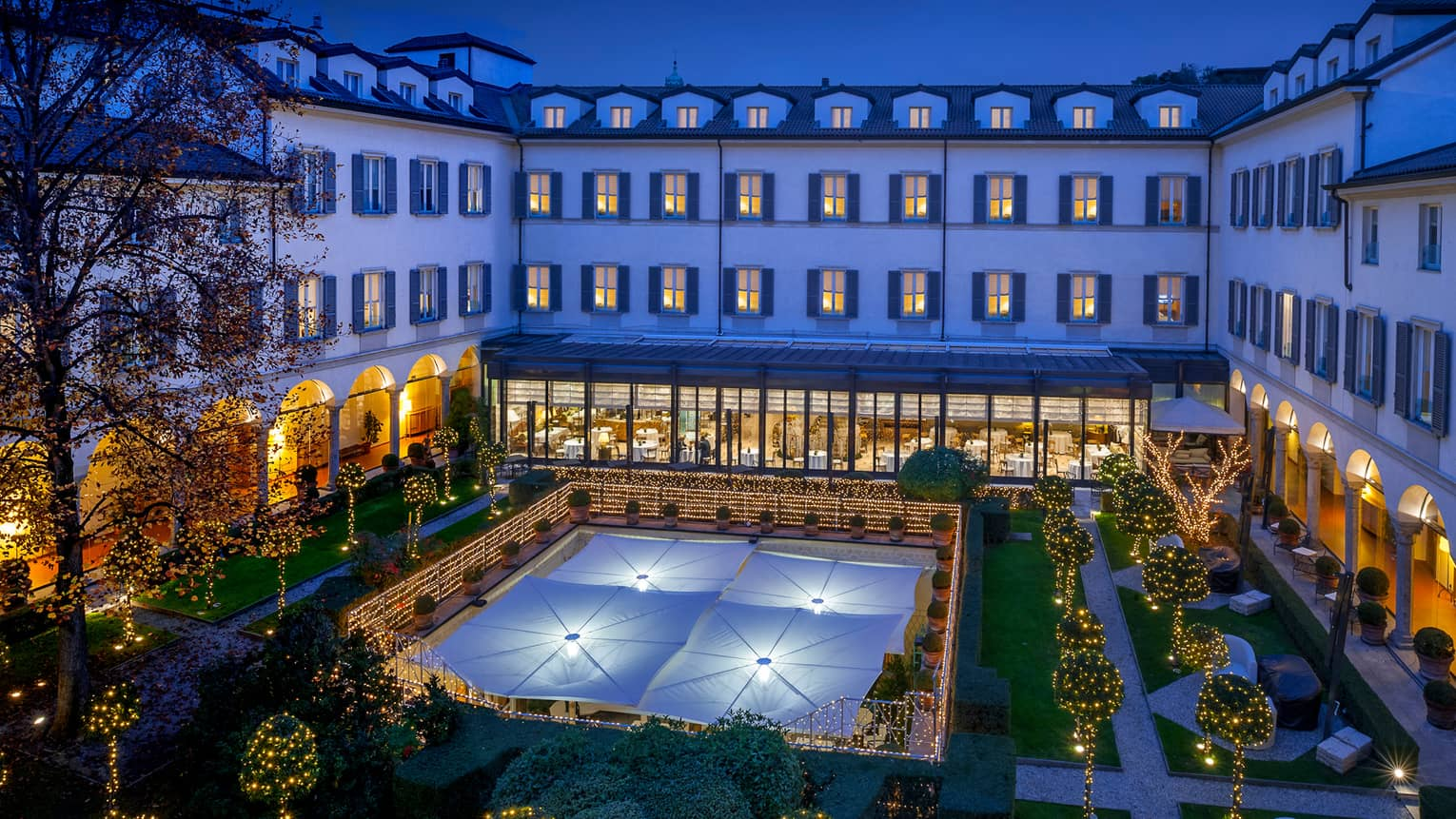Four Seasons Hotel Milan 15th-century cloistered courtyard, gardens, lights at night