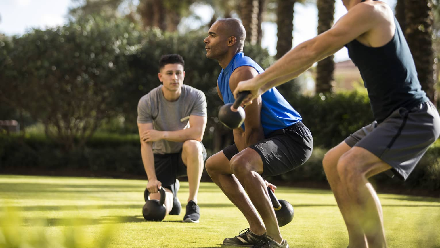Four Seasons trainer watches as two men squat, lift kettlebell weights on lawn