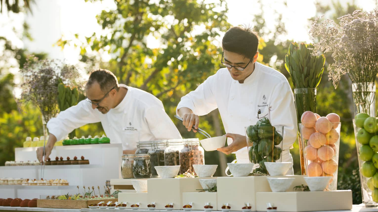 Two chefs arrange desserts on outdoor buffet