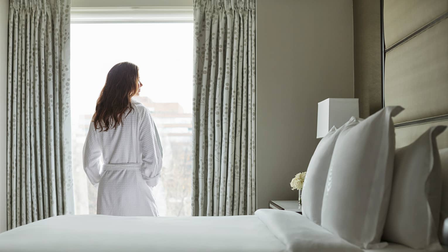 Back of woman in white bathrobe stands at sunny window in front of bed