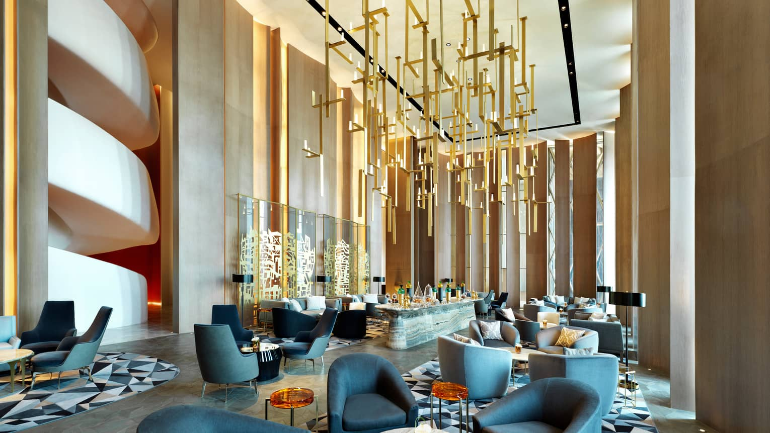 Modern dining chairs, tables in lounge with soaring ceilings, gold sculptures hanging from ceiling, wall