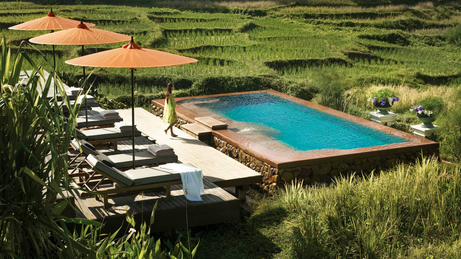 Woman in flowing dress walks past three patio umbrellas to infinity pool in rice plantation