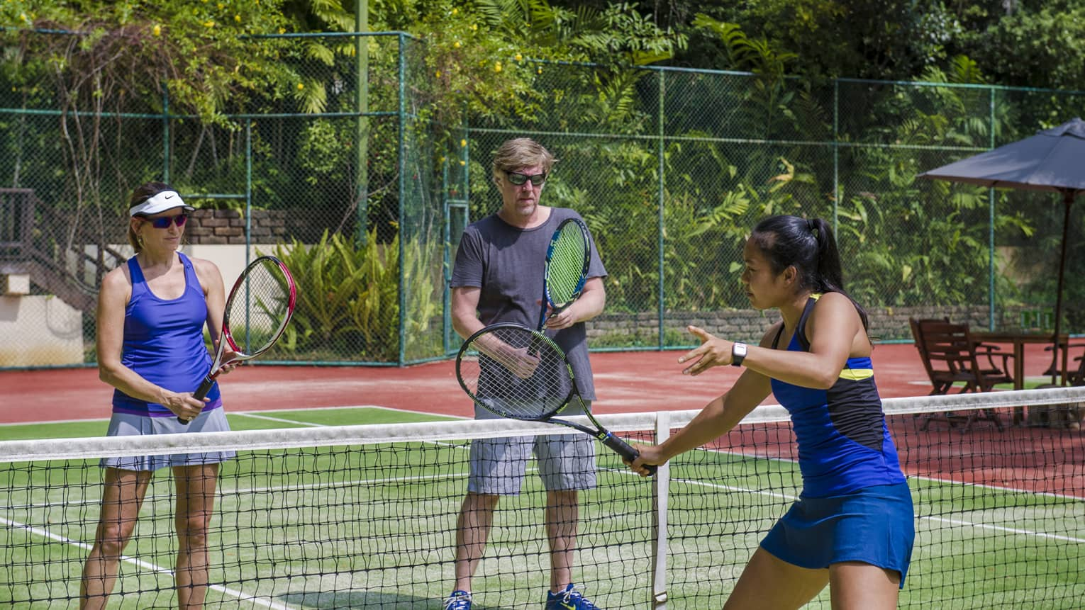 Woman demonstrates tennis serve at net while tennis pro Nichapa Rungtein, woman watch