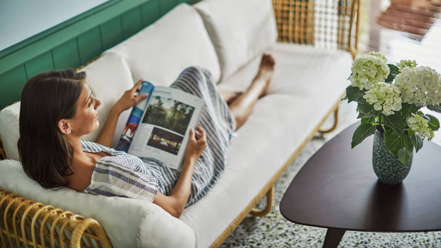 Private spa cabanas offer privacy. Woman stretches out on a sofa, reads magazine