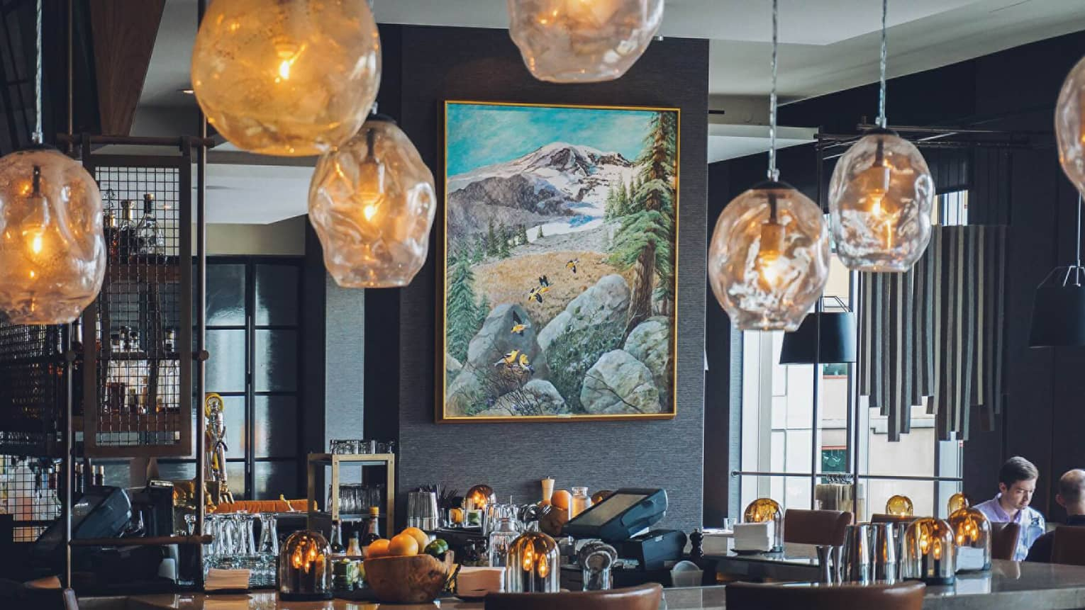 Amber-tinged glass lamps hang over bar in front of modern landscape painting in Goldfinch Tavern