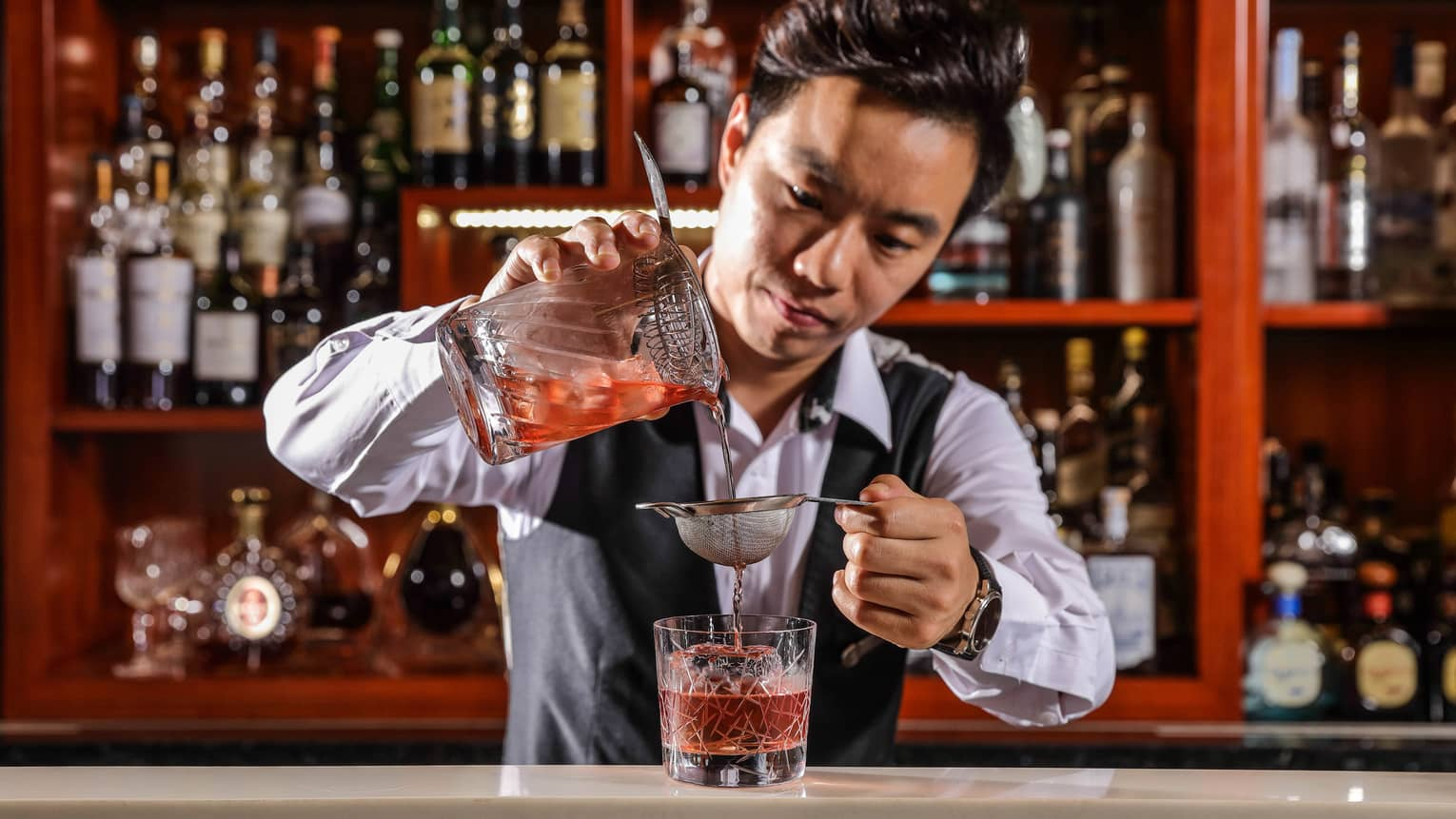 Bartender in black vest pours red cocktail from glass jug through strainer into glass