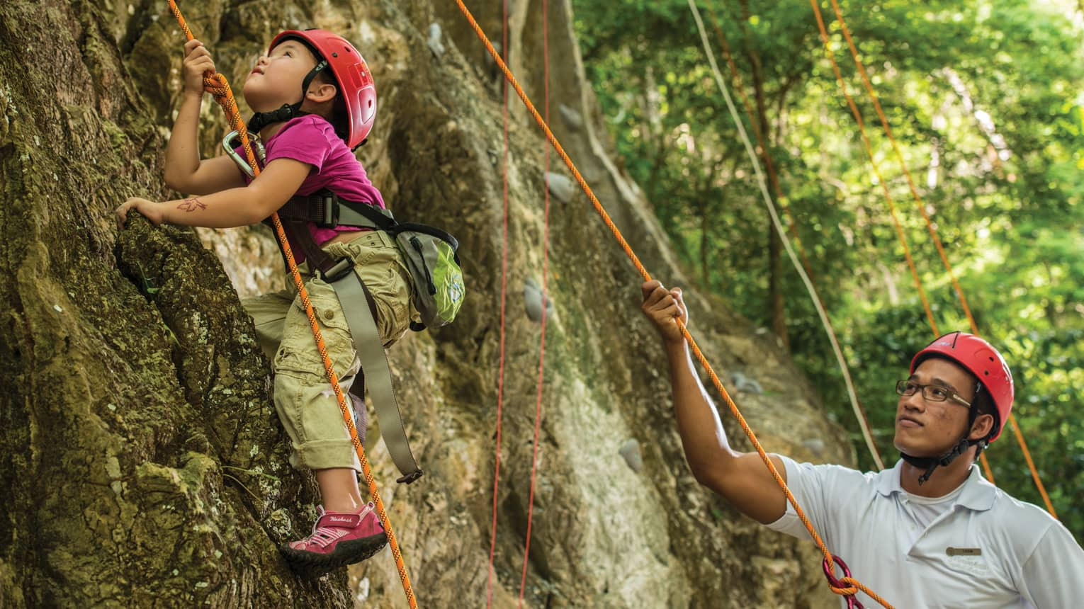 Man holds rope, helps young girl wearing helmet climb rock face
