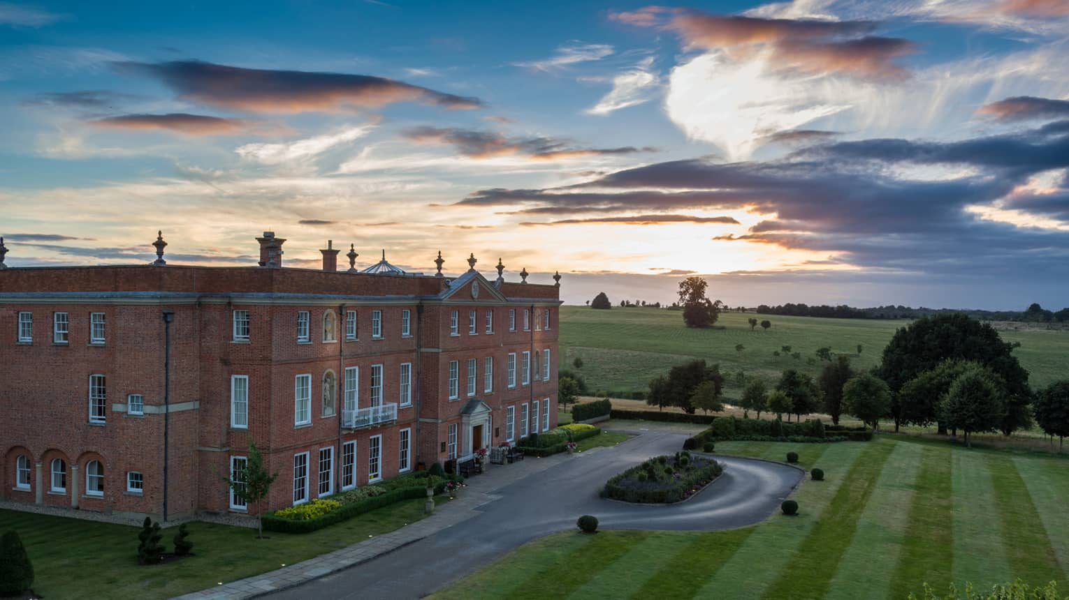View over historic manor hotel building by rolling green fields at sunset