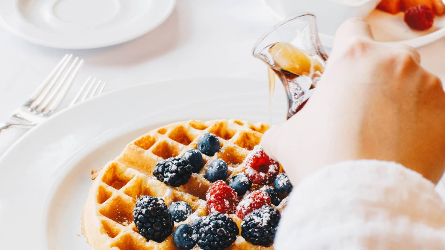 A guest pours syrup onto a Belgian waffle covered in berries