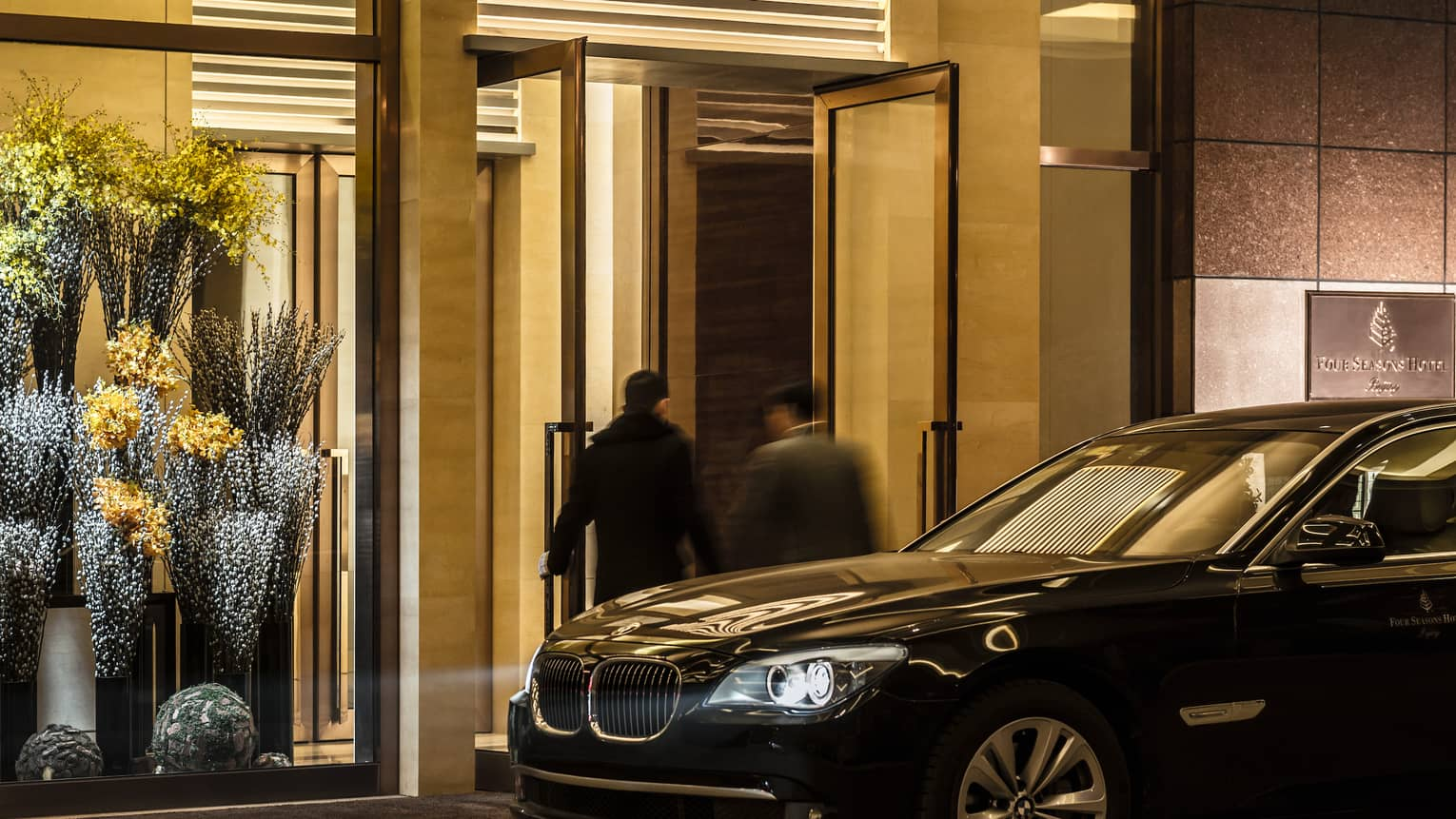 Two men walk into Four Seasons Hotel front entrance by luxury black car