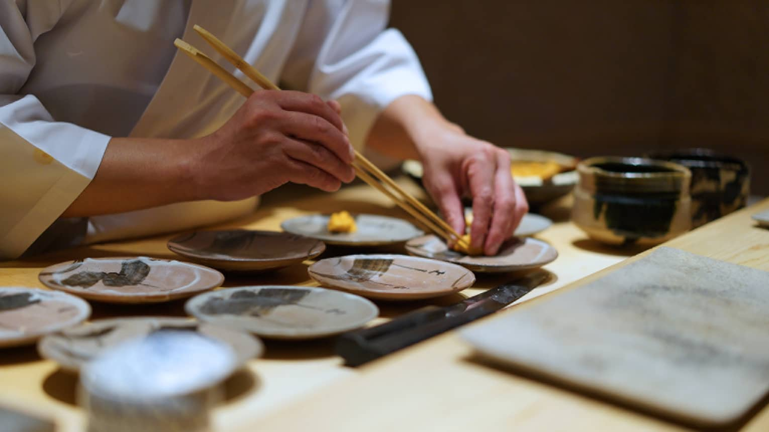 Close up of a chef using chopsticks to place a Food detail on a ceramic plate