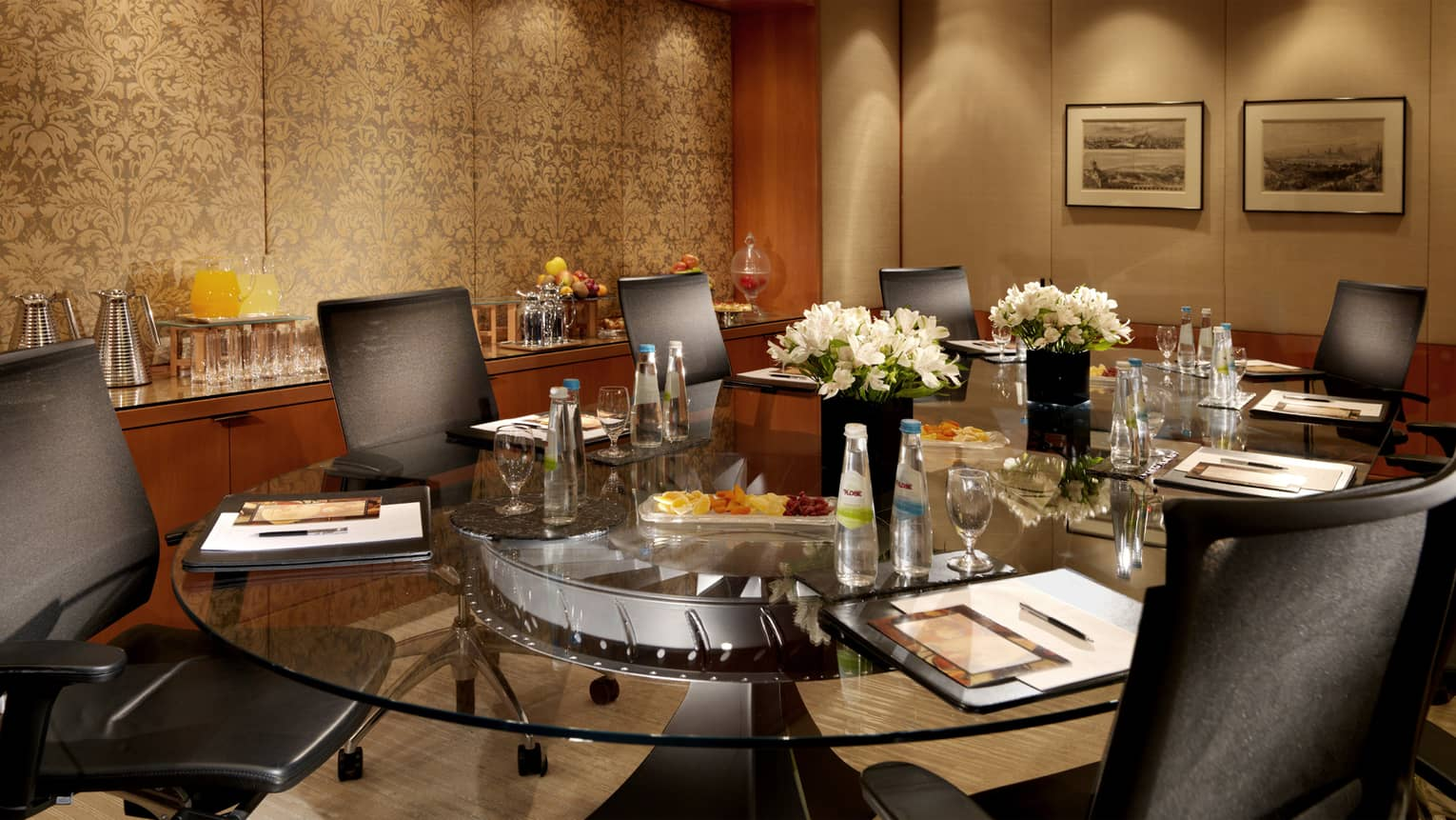 Spiga Meeting Room with round glass table lined with executive swivel chairs