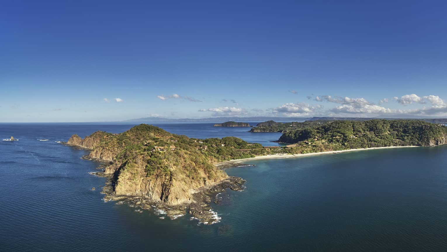 Aerial view looking over rocky cliff along blue waters of Peninsula Papagayo