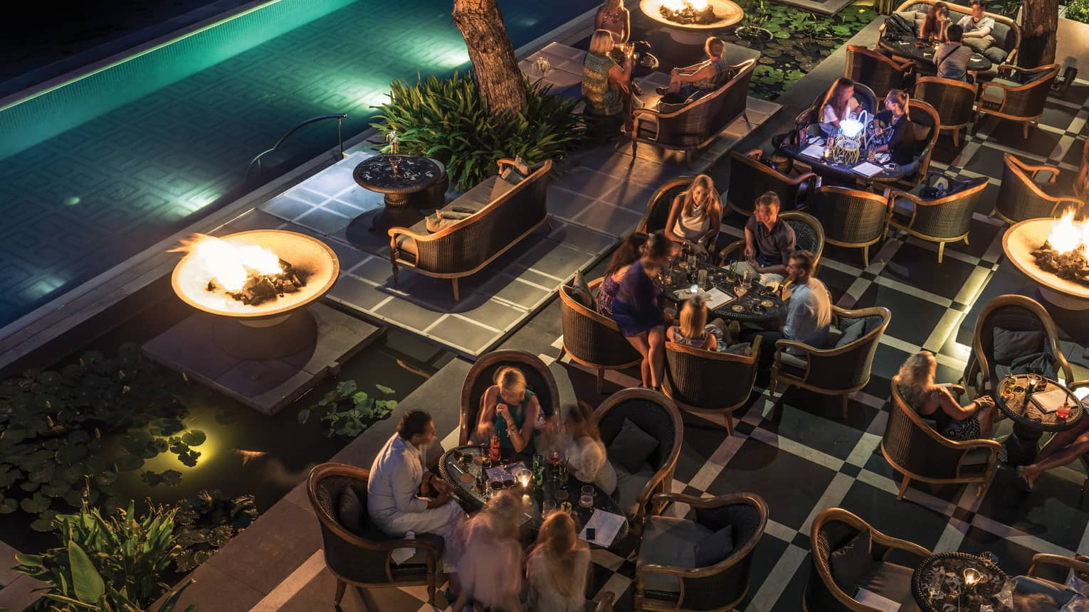 Aerial view of crowded patio at night with guests socializing at candle-lit tables, near illuminated swimming pool