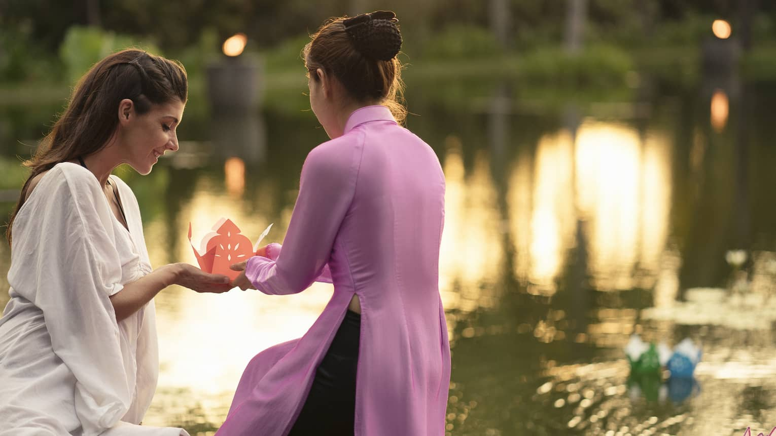 Two women prepare to release paper boat with love letter onto lotus pond