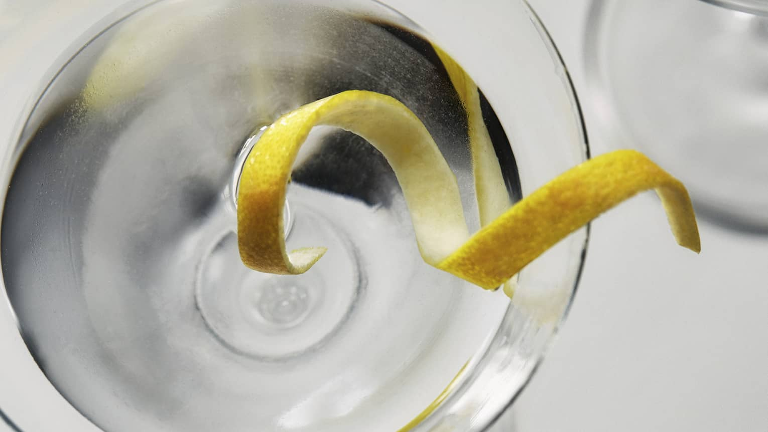 Aerial view of curled lemon rind in vodka martini, glass