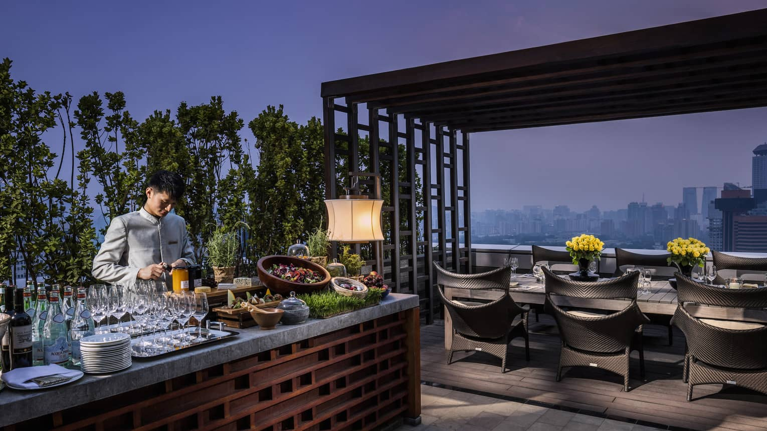 Bartender prepares drinks, cheeses, salads at long Imperial Suite rooftop bar by private dining table at night