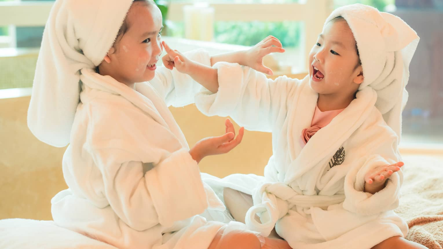 Two laughing young children in white bathrobes with towels around hair put lotion on each other's faces
