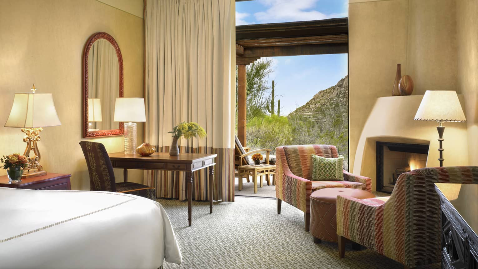 Premier Casita Room corner of bed, desk, armchairs by gas fireplace, mountain views through open balcony door