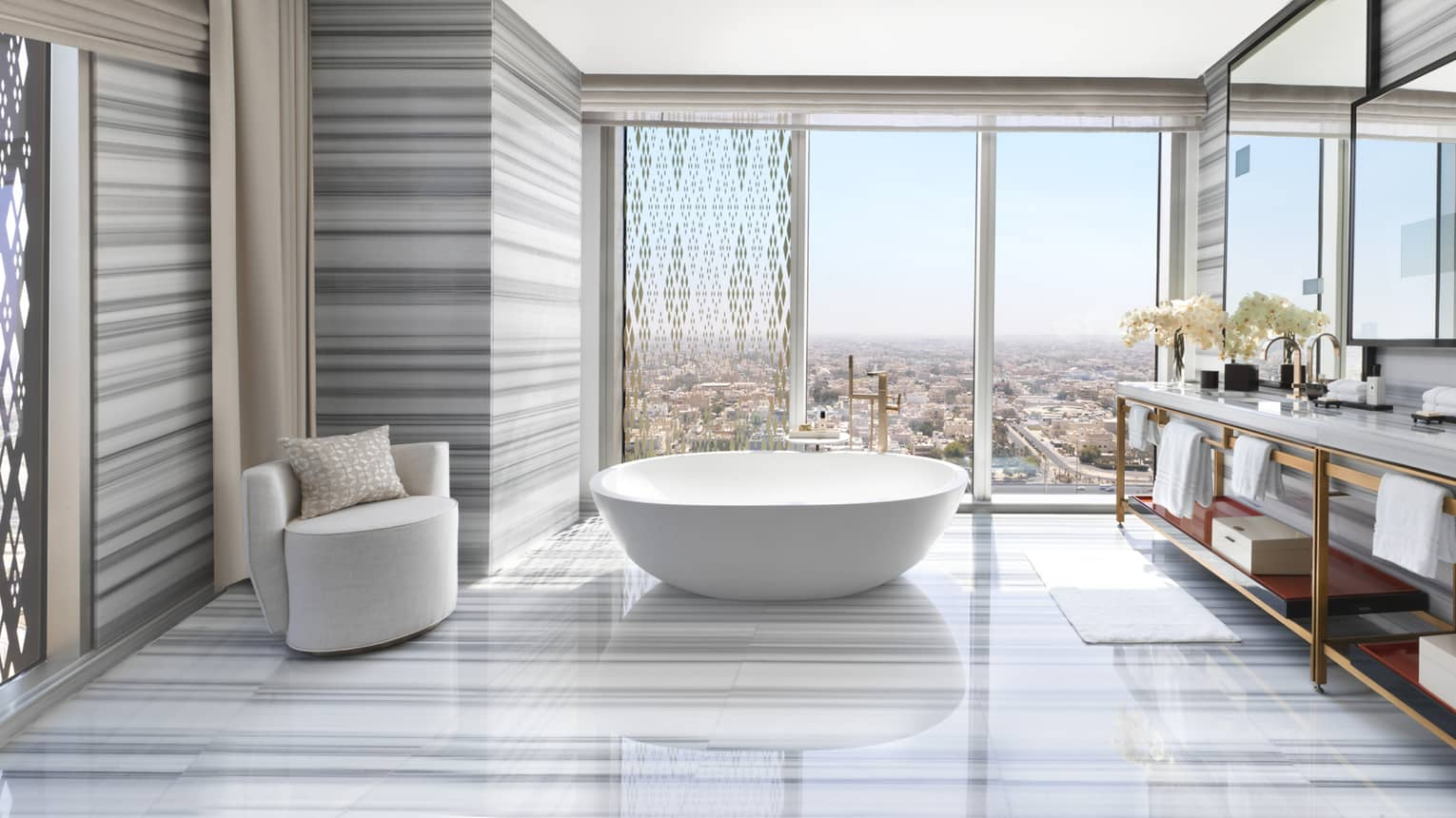 Large Royal Suite bathroom with modern striped marble floors, walls, freestanding tub, armchair