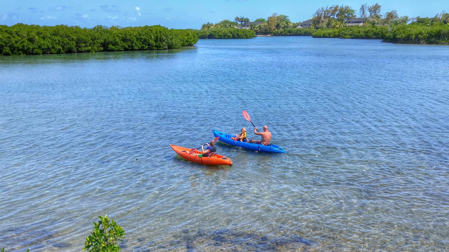 People in orange and blue kayaks on sunny lagoon