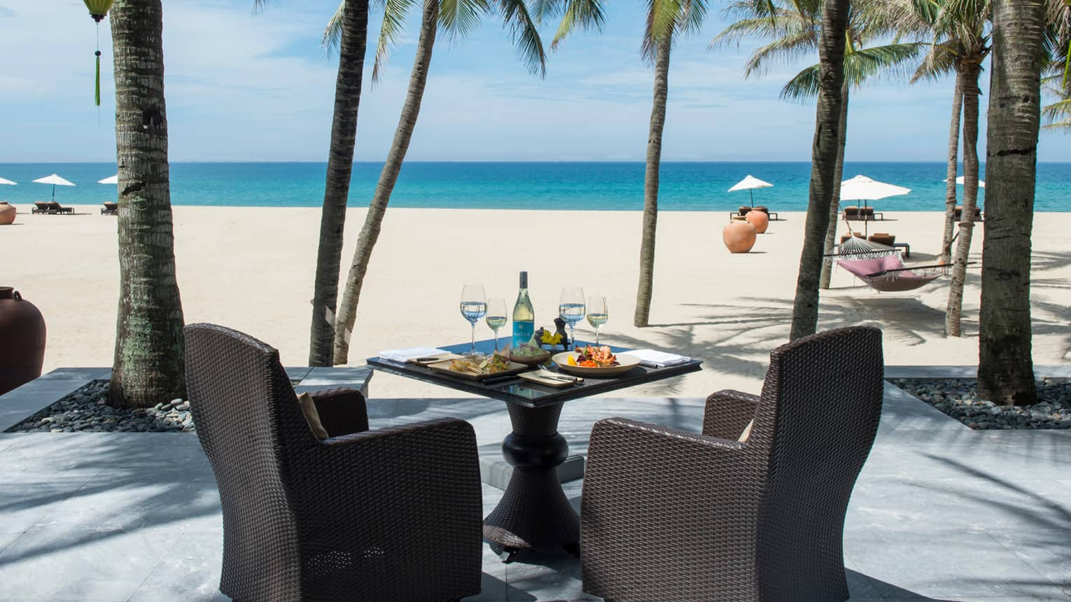 Dining table with meals, white wine, large black wicker chairs facing beach, ocean