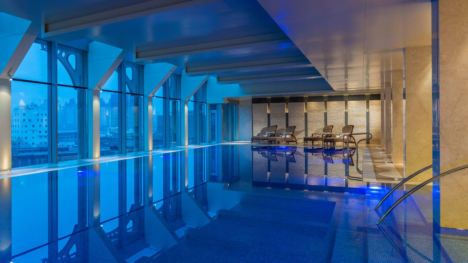 Indoor swimming pool along window at dusk