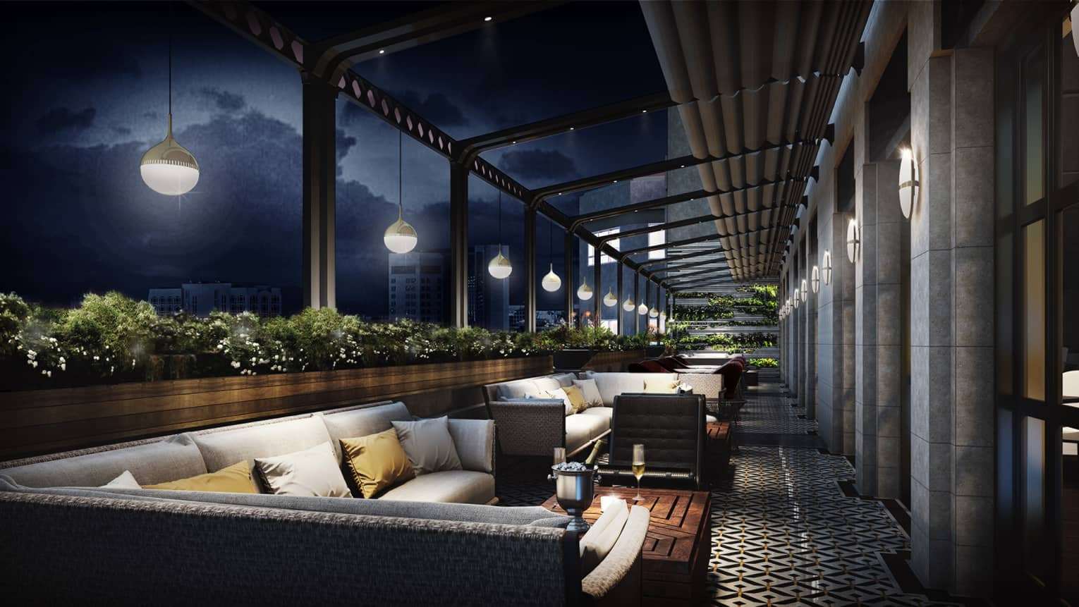 Long patio at night with L-shaped outdoor sofas, pillows, steel bucket with ice, champagne on wood table