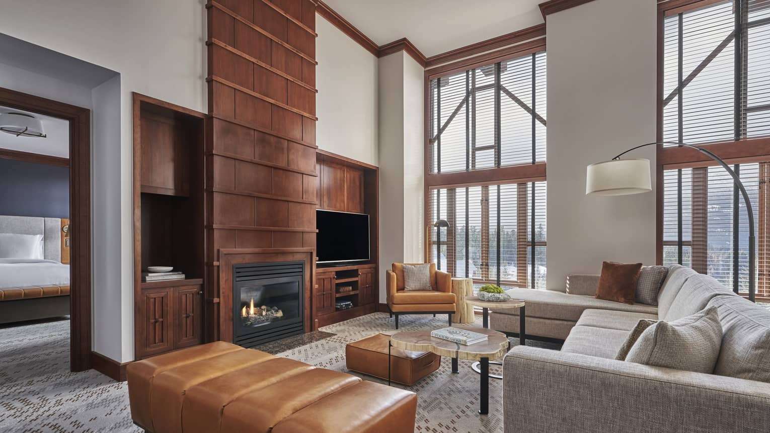 High-ceilinged living room of a suite, complete with a fireplace and light grey sofa