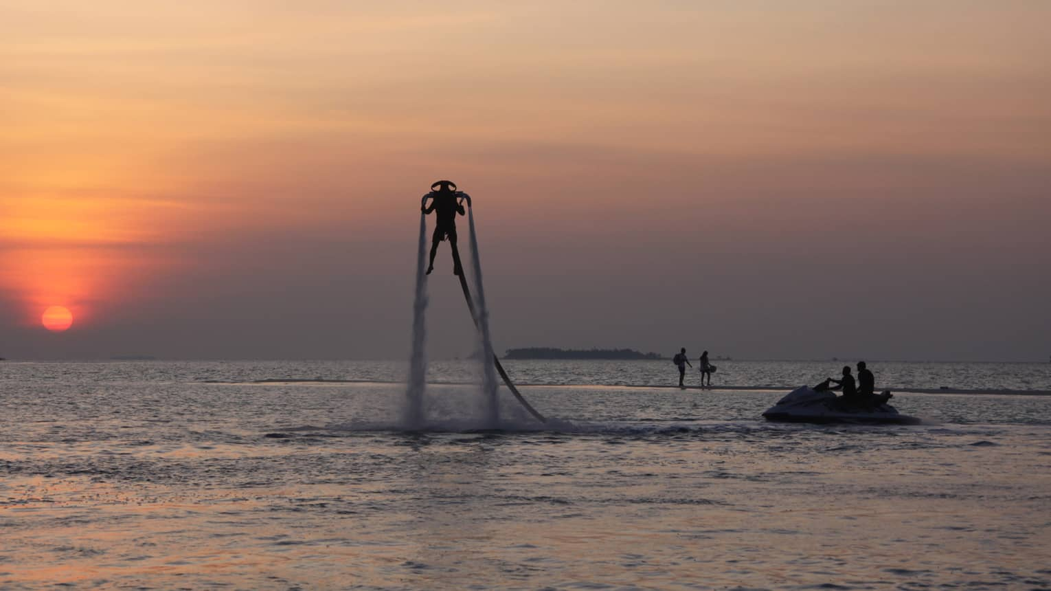 Silhouette of someone with X Jetpack suspended in air over water at sunset