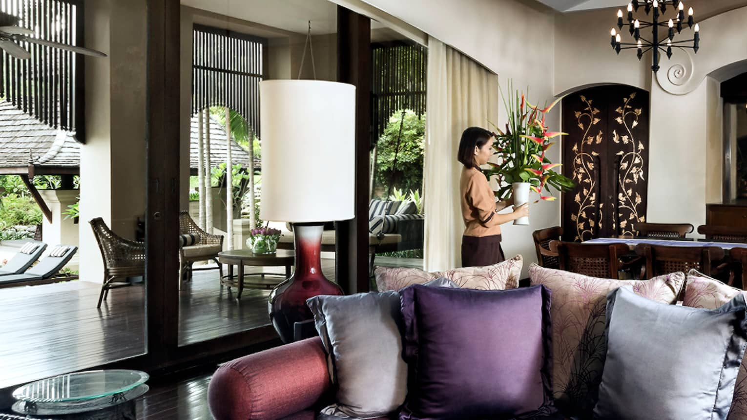 Hotel staff carries vase with tall tropical flowers past sofa, table in residence living room