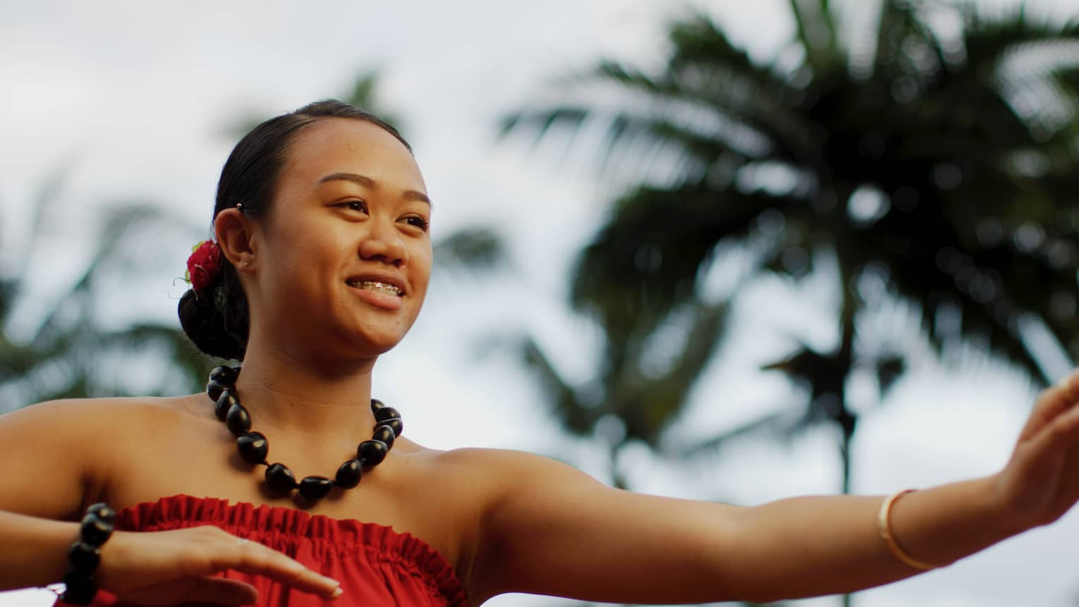 Close up of smiling Polynesian woman dancing under palm tree