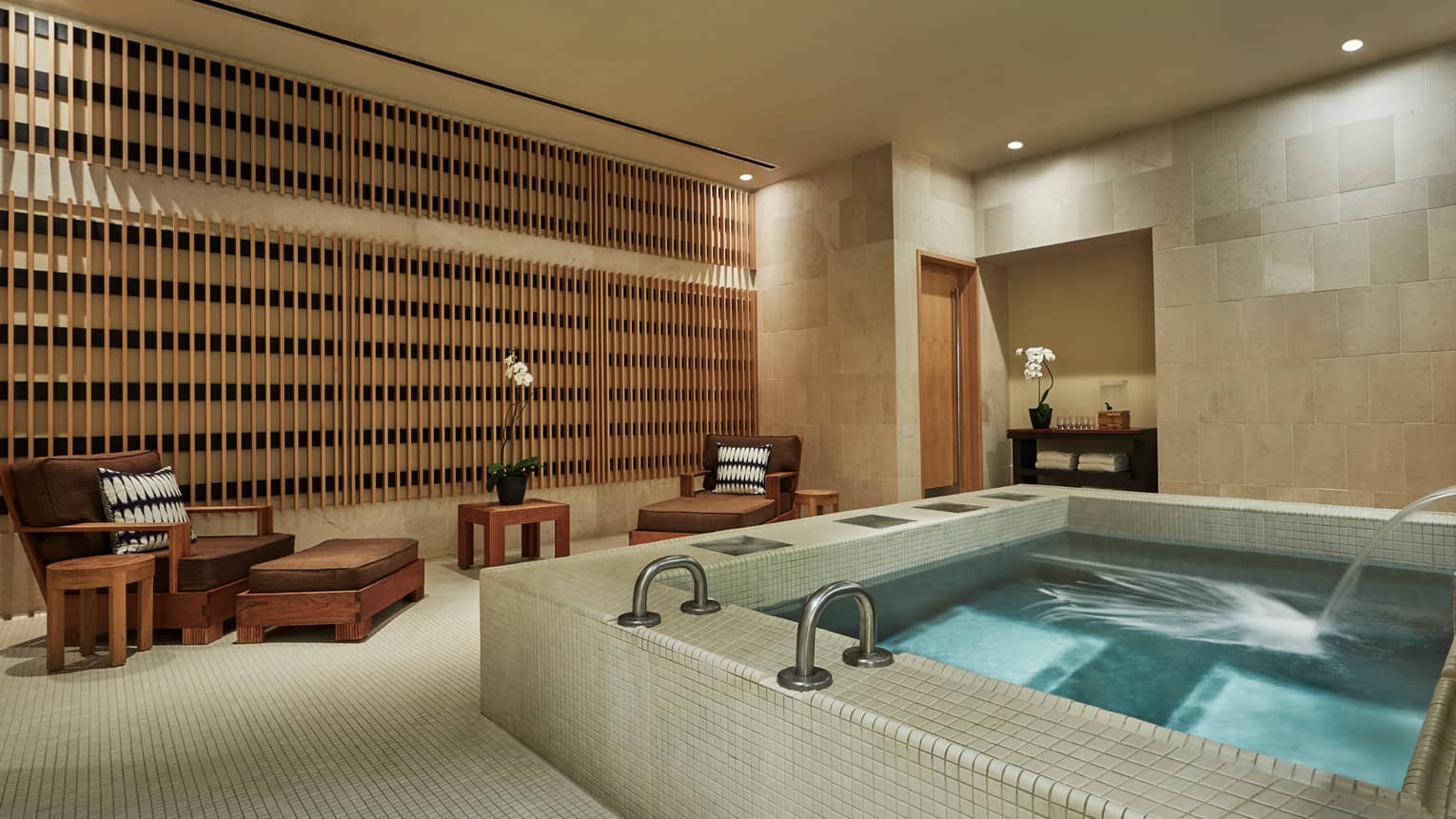 Large square spa tub with water jets in tile room with two brown lounge chairs