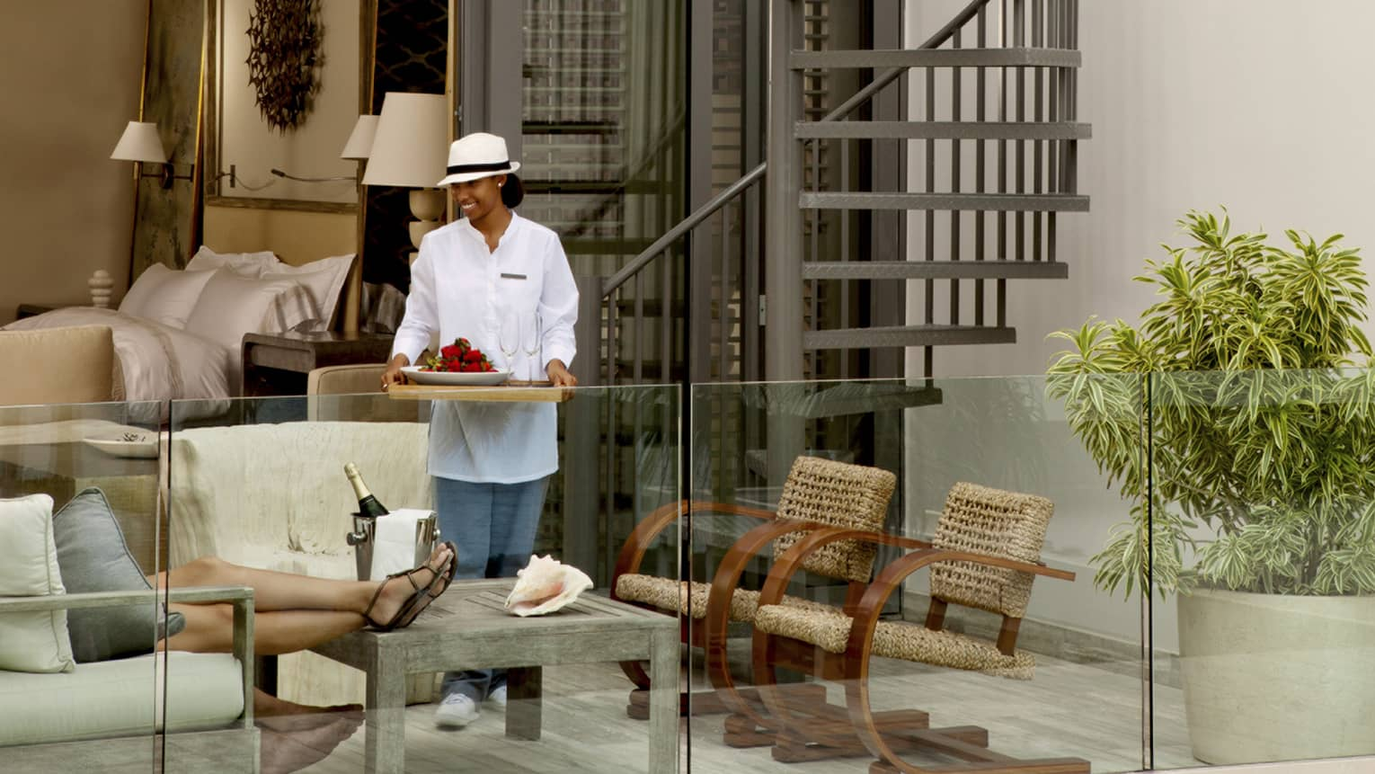 Server in white uniform and hat brings tray of fresh fruit, champagne glasses to guests on private villa patio