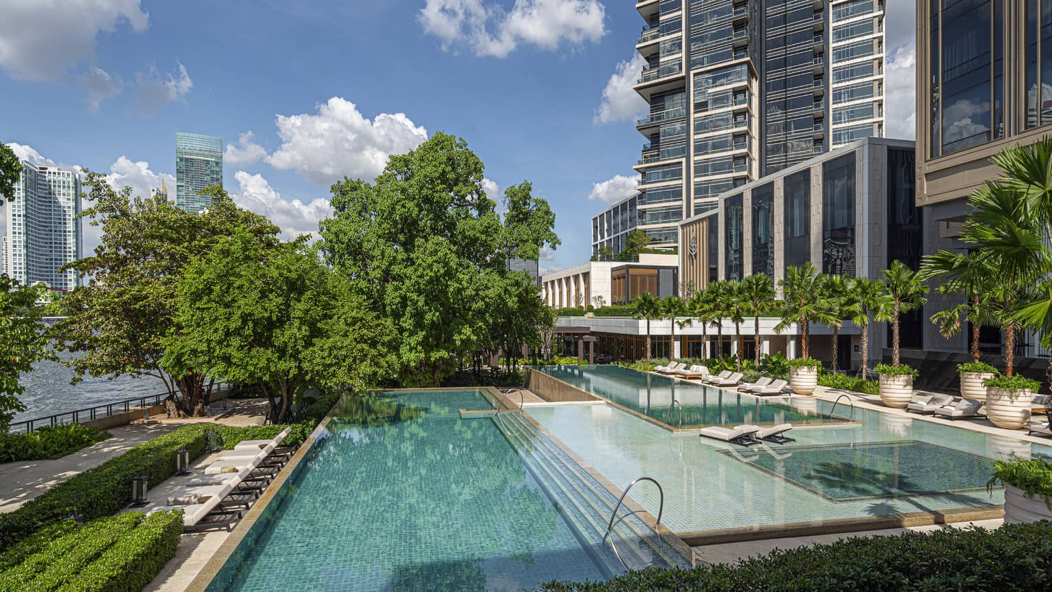 Rectangular hotel pools, staggered, with trees, overlooking Chao Phraya River