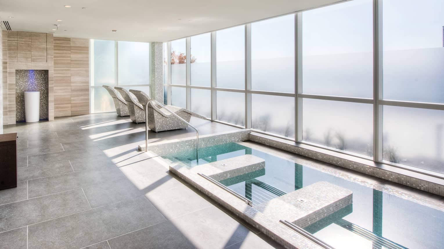 Spa plunge pool on grey tile deck, three stone chairs facing wall of windows
