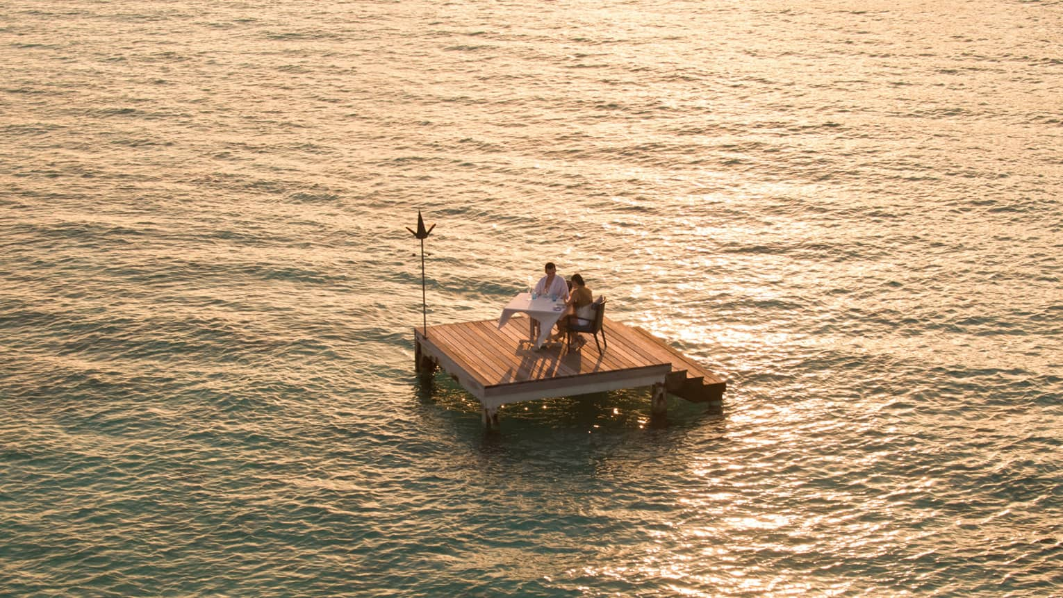 Aerial view of couple dining on small floating wood platform on moonlit lagoon