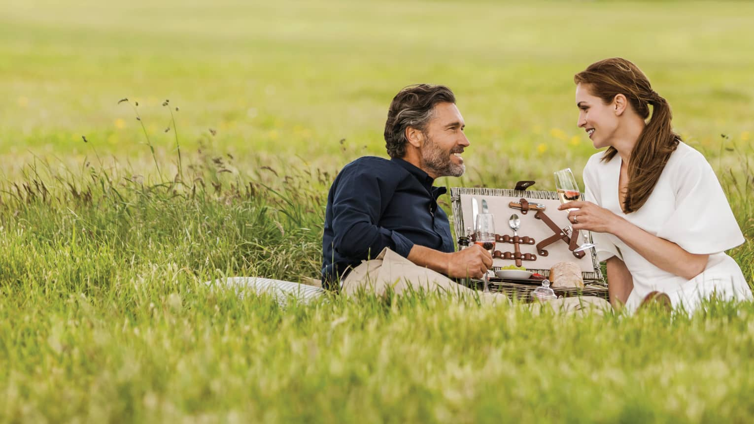 Couple with wine glasses lies in tall green grass with open picnic basket, hotel manor in background