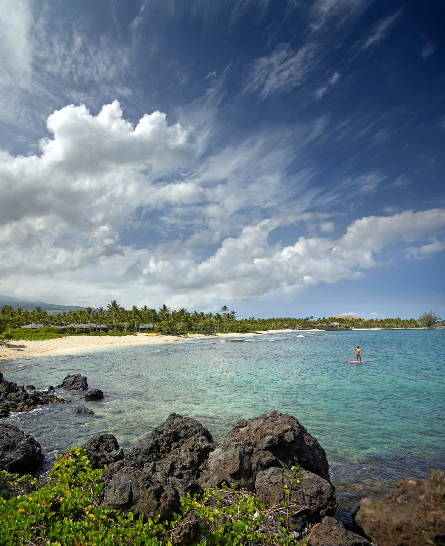 Person on stand-up paddleboard in lagoon past large black lava rocks, near white sand beach