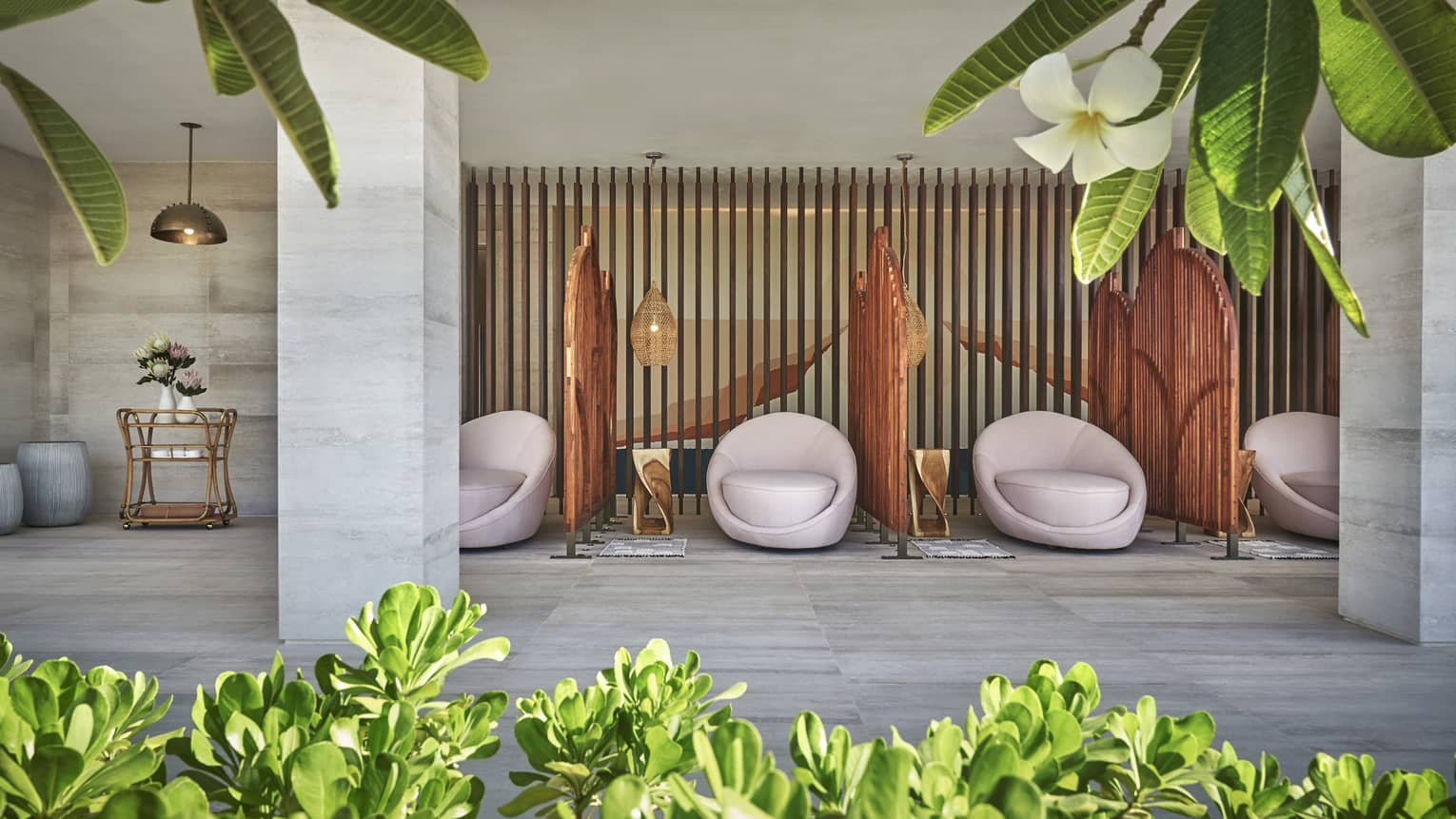 White egg-shaped spa chairs are separated by rattan walls in the four seasons resort los cabos spa terrace