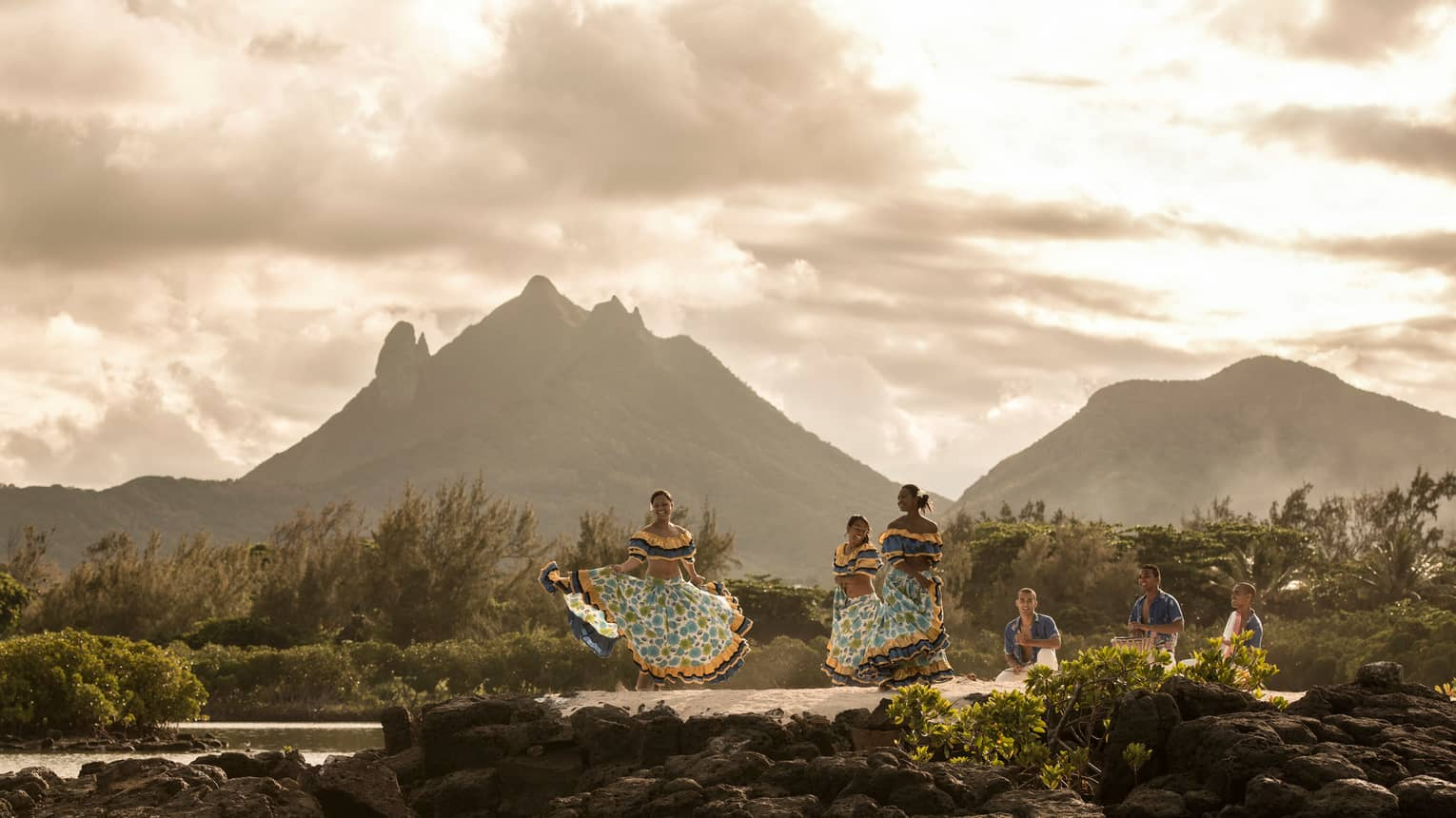 Traditional Mauritius Sega dancers in colourful dresses on rocks under mountains at sunset