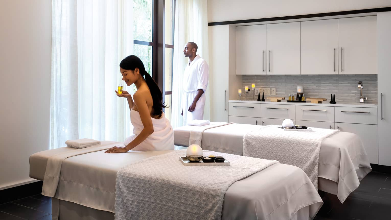 Woman wearing towel sits on edge of Couples Suite massage table, smells oil as man stands at window