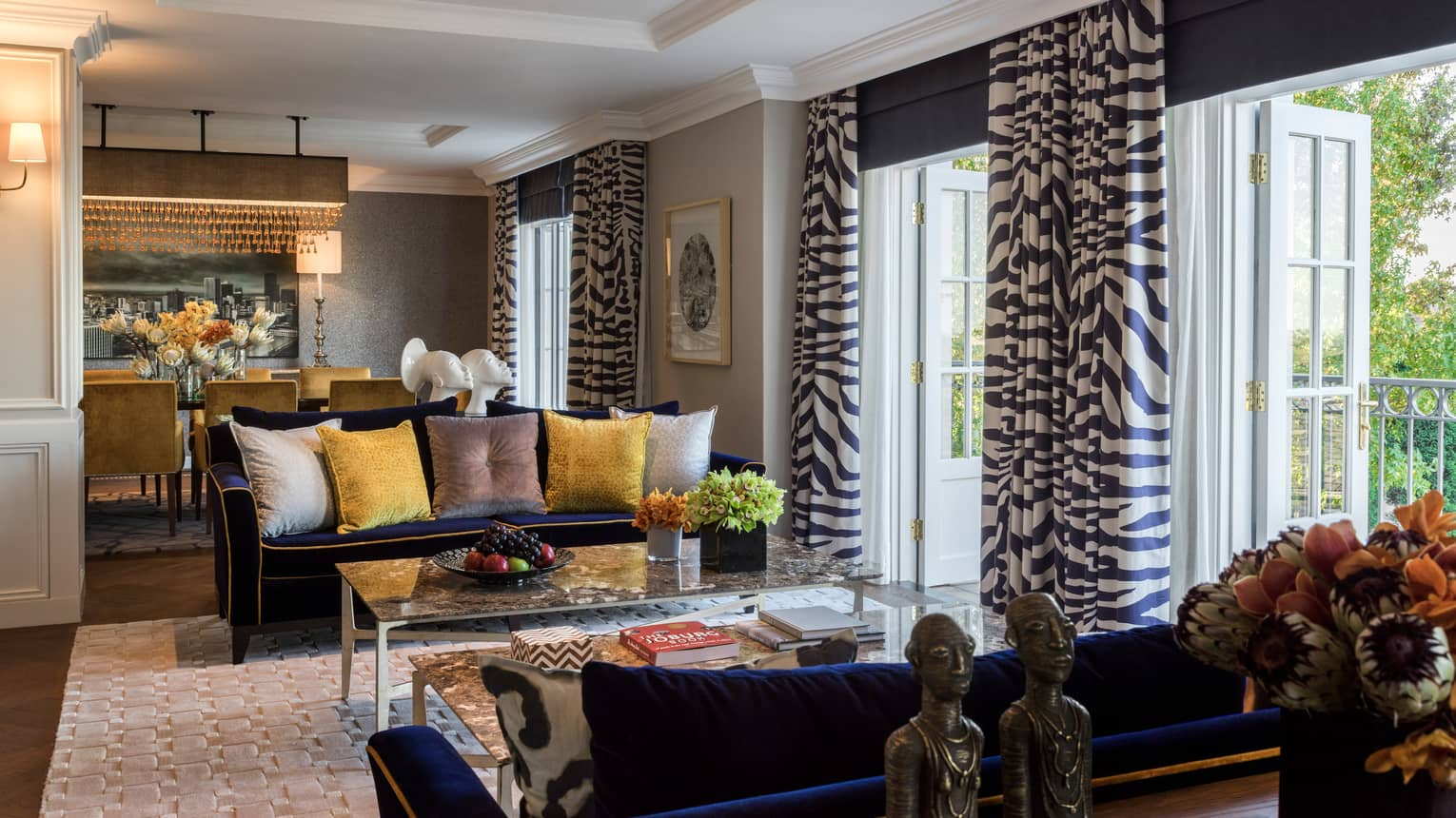 Royal Suite sitting area, two blue sofas with yellow, grey pillows, open patio doors with Zebra print curtains