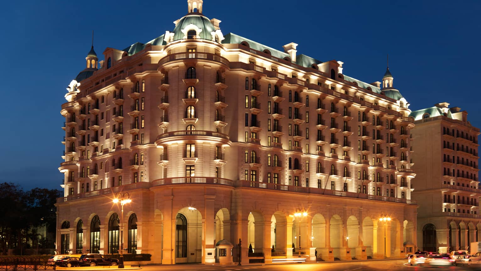 Night view of Baku Four Seasons Hotel Beaux-Arts-style building exterior with lights, illuminated roof