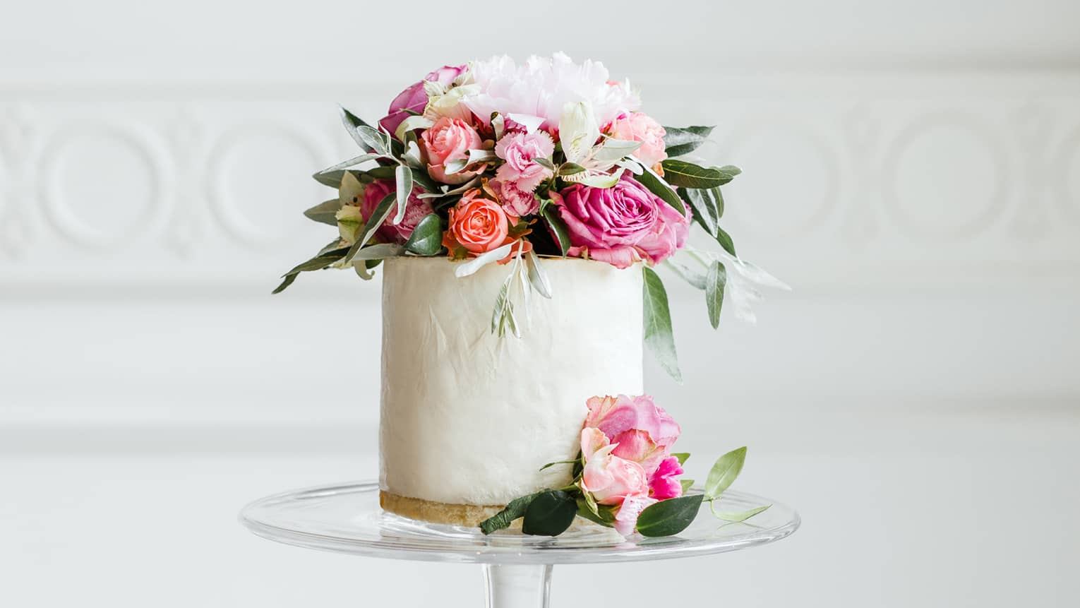 Elegant small white wedding cake topped with fresh pink and white roses