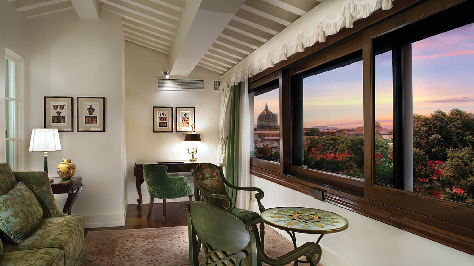 Duomo View Executive Suite green sofas, chairs and table by large picture window overlooking Florence, sunset