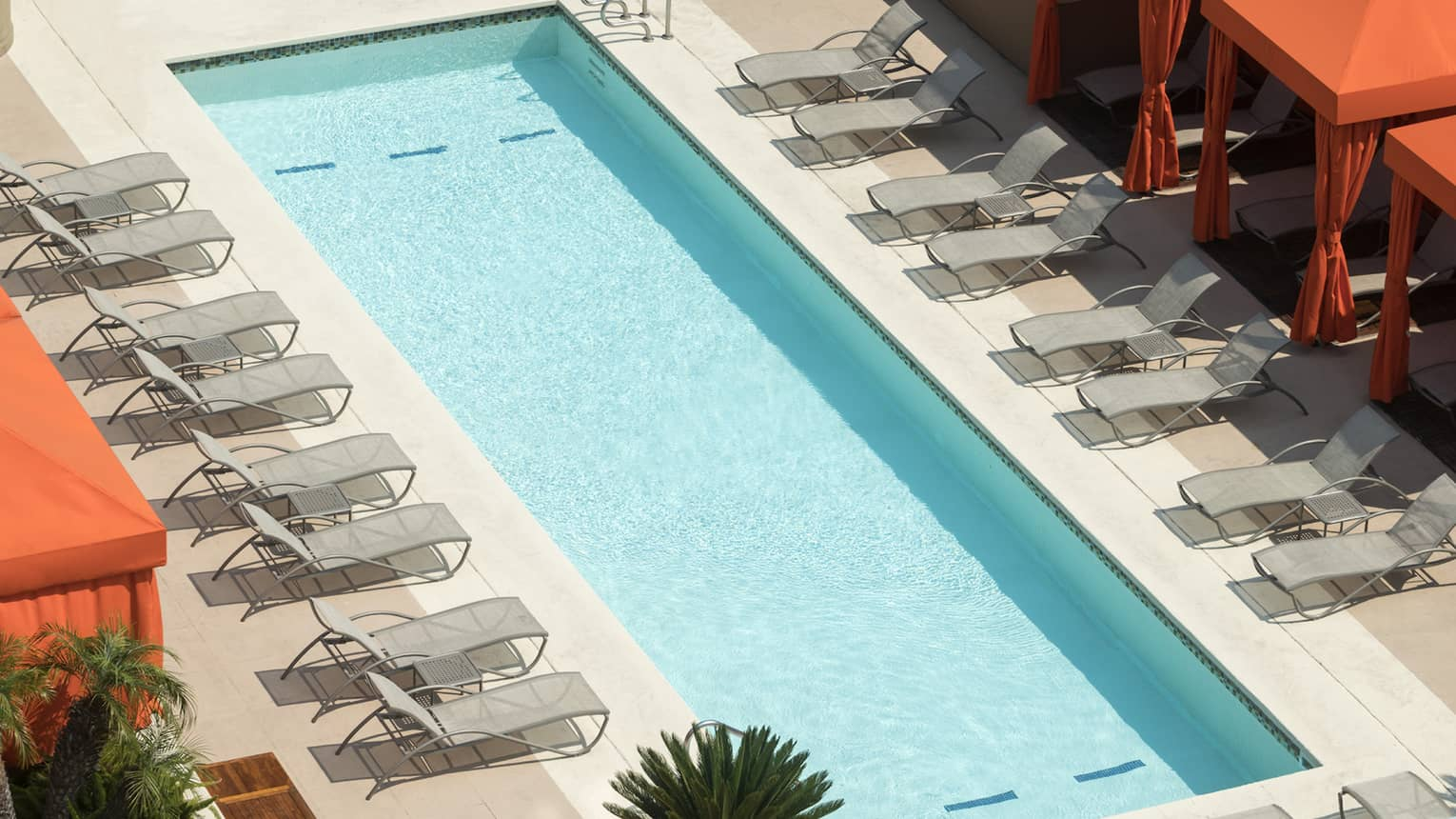 Aerial view of outdoor rooftop swimming pool lined with lounge chairs, cabanas