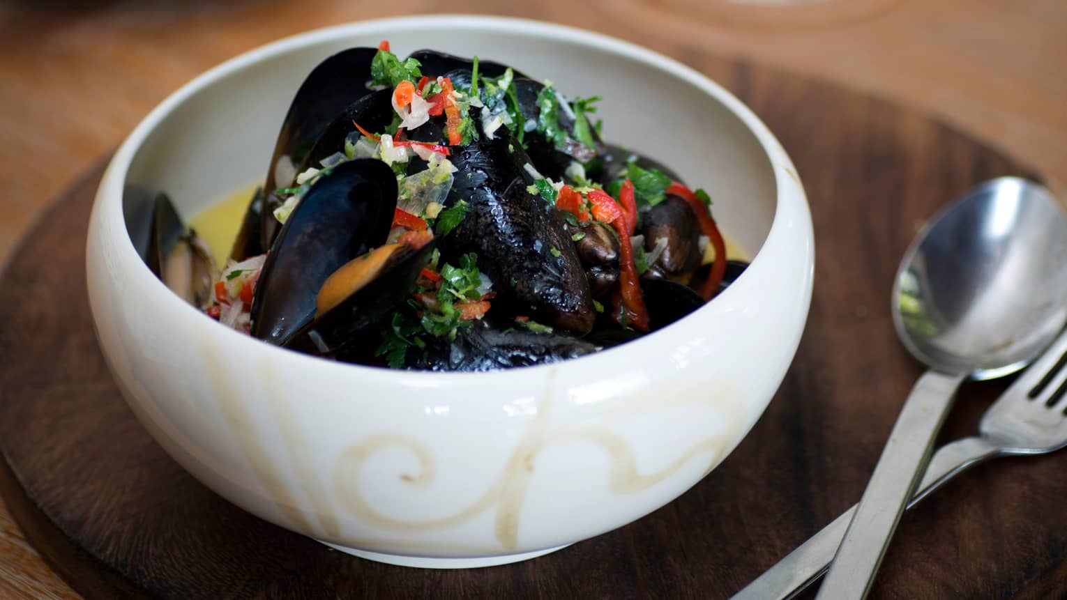 White bowl with Pot Steamed Black Mussels, garnished with chopped lemongrass, ginger, citrus